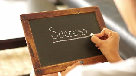 cíle : A woman writing Success on a vintage chalk board