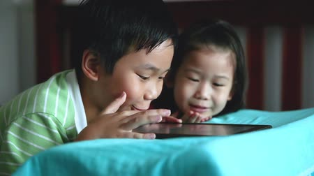 ntsc : Tilt up of asian children playing digital tablet together. Focus at chinese boy, his younger sister smiling and lying prone on bed. Conceptual about using E-learning technologies and sibling relationship.