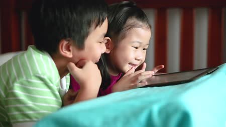 ntsc : Asian children using digital tablet. Happily brother smiling and cheering his sister near by. Cute girl playing games excitedly on touchpad and lying prone on bed. Focus shifting from boy to girl.