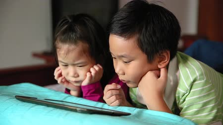 ntsc : Asian children using digital tablet and lying prone on bed. Conceptual about using E-learning technologies and sibling relationship.