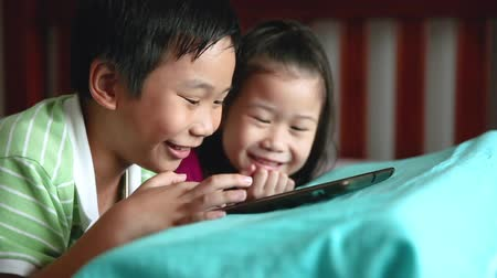 ntsc : Asian children using digital tablet. Happily sister smiling and cheering her brother near by. Cute boy playing games excitedly on touchpad and lying prone on bed.