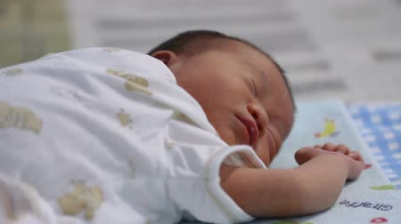 squirm : Asian baby sleeping face. Close up of a four-month adorable baby resting and squirming. Healthy children concept.