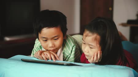 ntsc : Pan video of asian children looking at digital tablet. Focus at chinese boy, younger sister lying prone on bed, near by. Conceptual about using E-learning technologies. Cinematic tone. Stock Footage