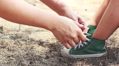 fofo : Kindness mother helping her daughter to tie shoelaces. Child wearing green sport shoes. Concept about care and good relations in happy family with kids. Outdoor on summer day.