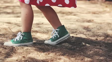 Child in pretty red dress and green sport shoes. Close up, childrens feet walking toward in park path. Outdoor on summer day. Stok Video