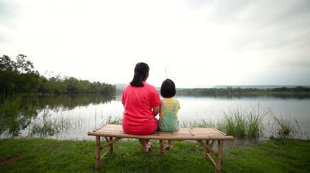 Asian mother with her daughter side by side on bamboo litter. Happy girl pulling rod in her hands while fishing against landscape of lake. Concept of connecting children with nature. Travel on vacation.