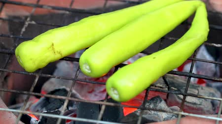 Hand turn piece of fresh green chilies grilled on barbecue stove.