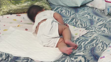 Three months old baby girl lies on a bed and learning to roll from back to stomach.
