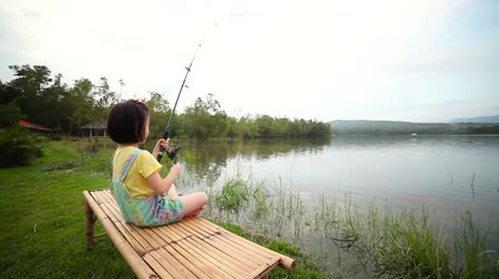 Lovely asian child sitting on bamboo litter. Happy girl pulling rod in her hands while fishing against landscape of lake. Concept of connecting children with nature. Travel on vacation.