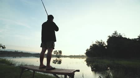 Silhouette of a man holding a fishing pole while standing alone fishing at the lake. In the midst of a peaceful and refreshing nature in the morning.