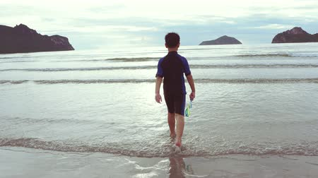 A boy in a swimsuit is walking from the beach to the sea. Fresh air in the morning, the sun is rising.child on summer vacation.4K UHD Stok Video