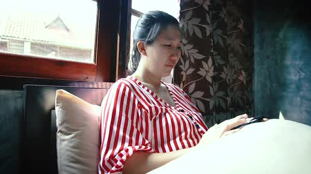 Asian woman sitting near window and using a smartphone while relaxing on bed in the bedroom.