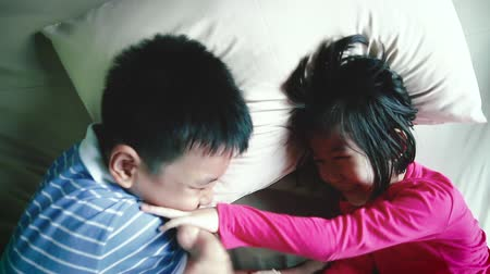 sourozenci : Top view of happy family having fun in bedroom. Enjoying being together. Laughing brother are tickle play with her sister while lying in bed.