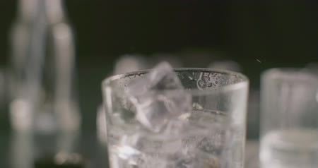 tonikum : Dropping ice cubes in glass 4k slow motion