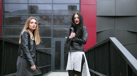 városi : Two girls walking on the street, looking at the camera and smiling