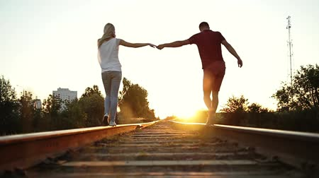 баланс : Boy and girl go on rails to the sunset. They hold each others hand.