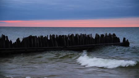superior : The sun set on Lake Superior as waves roll in and break around and old wooden groyne at Michigan