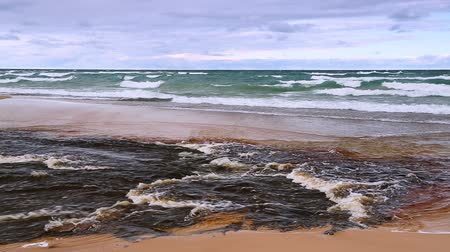 pictured : The Hurricane River flows across the beach and into Lake Superior on a blustery day at Pictured Rocks National Lakeshore in the Upper Peninsula of Michigan. Stock Footage