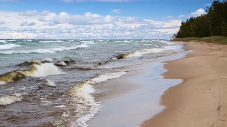 upper peninsula : Waves break on the sandy Twelve Mile Beach at Pictured Rocks National Lakeshore in Upper Peninsula Michigan on a windy day with blue sky and white clouds. Looping.