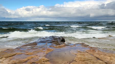 pictured : Lake Superior waves roll in against a rocky coast under a cloudy blue sky at Pictured Rocks National Lakeshore in the upper Peninsula of Michigan in this seamlessly looping video footage.