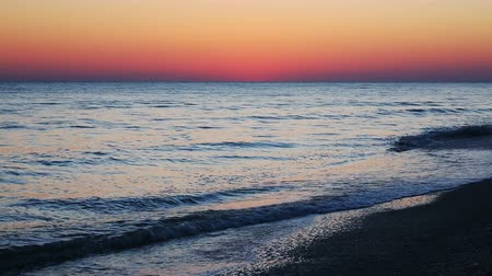 video loop : A colorful sky, after sunset, tops the sea with gentle waves breaking on and sandy beach.
