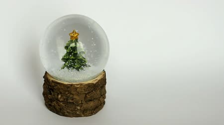 Snow globe with Christmas tree and whirling snowflakes