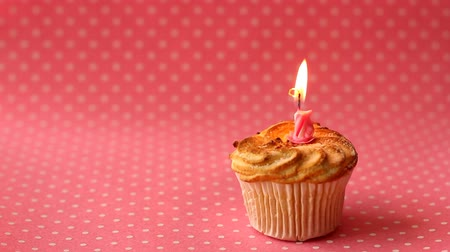 Cupcake with burning candle. Time lapse video