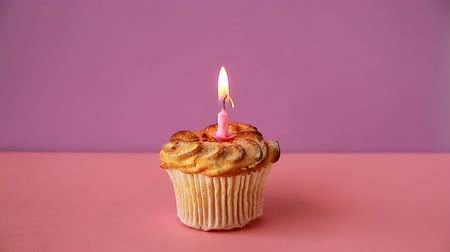 Cupcake with one lighted candle for the birthday. Time lapse video Стоковые видеозаписи