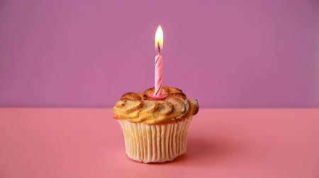 Cupcake with one lighted candle for the birthday Стоковые видеозаписи