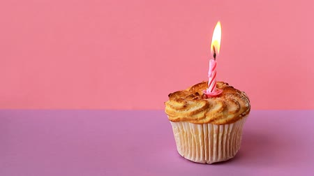 single shot : One lighted candle on birthday cake Stock Footage
