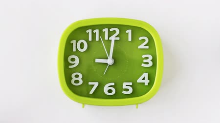 Green clock with white numbers and arrows on white background, Time Lapse