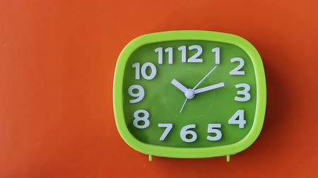 Green clock with white numbers and arrows on an orange background, Time Lapse