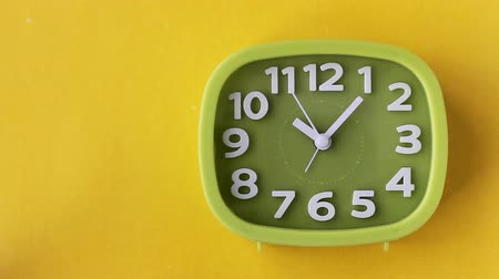 Green clock with white numbers and arrows on yellow background, Time Lapse Стоковые видеозаписи