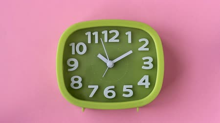 Green clock with white numbers and arrows on a pink background, Time Lapse