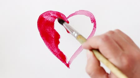 Heart painted red watercolor on white background, time lapse