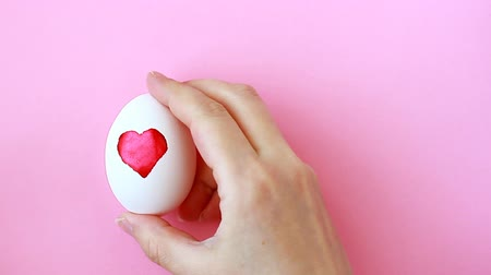 Female hand holding eggs with painted watercolor heart for Easter on pink background