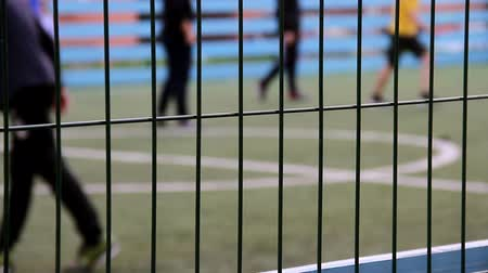tekmeleme : Teens boys playing soccer on football field, fenced with fence for security, defocused shooting, focus on fence