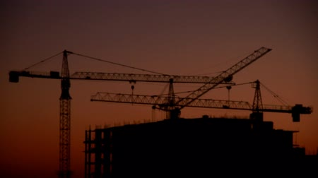 Construction of a high-rise building against the background of sunrise, time lapse