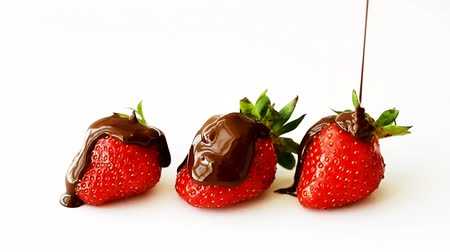Three ripe strawberries watered with melted chocolate on top, isolated on white background
