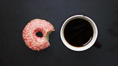 Eating pink donut and drinking a cup of coffee on a dark background view from above, stop motion animation