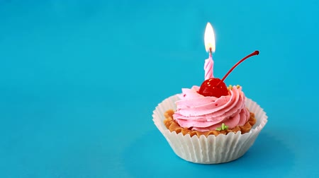 Birthday cake with cherry and burning candle for birthday on blue background. Time lapse video