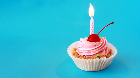 Birthday cake with cherry and burning candle for birthday on blue background