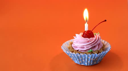 Birthday cake with cherry, pink cream and burning candle for birthday on orange background. Time lapse video Stock Footage