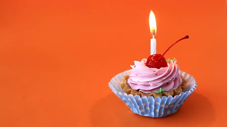 Birthday cake with cherry, pink cream and burning candle for birthday on orange background