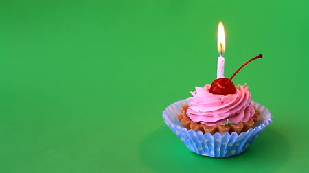 Birthday cake with cherry, pink cream and burning candle for birthday on green background