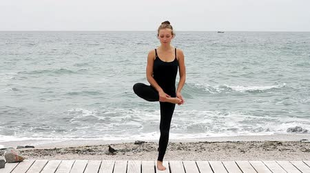 Young woman doing yoga at the seaside in the morning on summer day. Young woman doing yoga and looking at camera Wideo