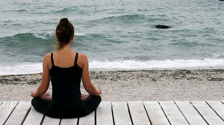 Girll sits in silence in lotus position and meditating by the seaside