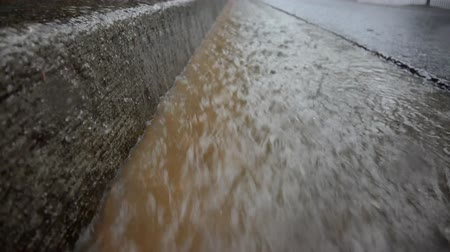 During a heavy rain, muddy water flows downhill in a gutter with a concrete curb. This video is a seamless loop.