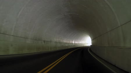 řídit : A car quickly enters, drives through, and leaves a tunnel while headed down hill in the Great Smoky Mountain National Park