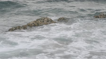 pijany : Waves wash over an exposed rock as they head to shore. Wideo